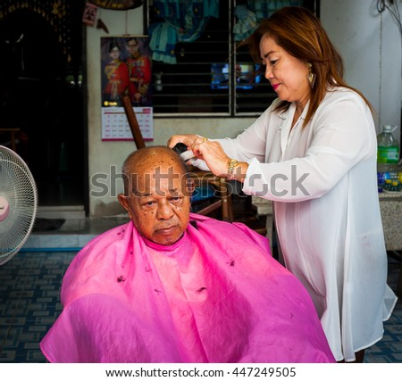 BANGKOK THAILAND - JUNE 3, 2016 : Woman barber haircut to The Old man in Bangkok Thailand.