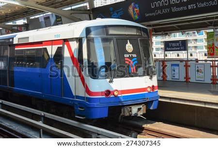 BANGKOK, THAILAND - MAR 22, 2015: A BTS Skytrain on elevated rails above Sukhumvit Road in Bangkok, Thailand. Each train of the mass transport rail network can carry over 1,000 passengers. - stock photo