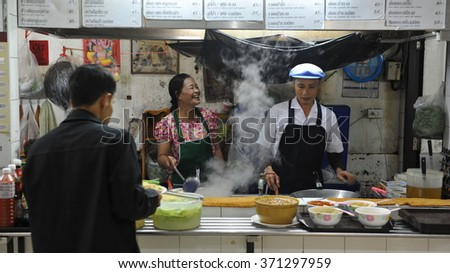 BANGKOK, THAILAND - MAR 26, 2013: Street vendors cook at a roadside restaurant kitchen. The Thai capital is renowned for its varied and palatable cuisine. - stock photo