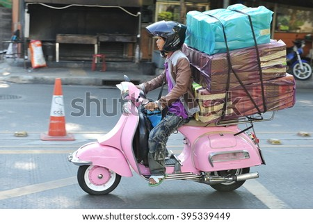 Bangkok, Thailand - March 19, 2013: A motorcyclist rides an overloaded Vespa on a city street. The use of motorbikes by couriers to transport goods and make deliveries is common in the Thai capital. - stock photo