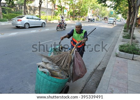 Bangkok, Thailand - March 19, 2013: A street sweeper walks on a city road. Bangkok Metropolitan Administration (BMA) employs street sweeper and refuse collection services throughout the Thai capital. - stock photo