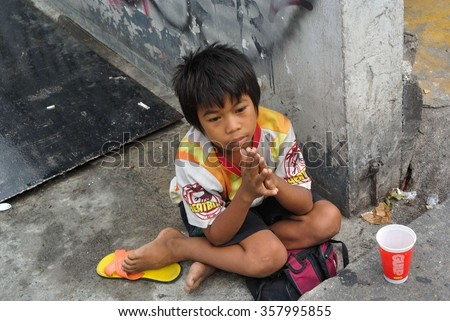 Bangkok, Thailand - March 2014 : Dirty and small child begging in the buzy street of Bangkok. The boy look to the crowd with sad face hoping for sympathy. Education is neglected to survive. - stock photo