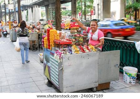 BANGKOK, THAILAND - MARCH 22, 2009: Thai flower vendor sells  Buddhist flowers on the street. - stock photo