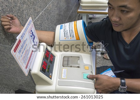 BANGKOK,THAILAND - march 10: thailand,thai men using sphygmomanometer for check his healty, march 10 205 in Ratchadamnoen Rd. Bangkok,Thailand - stock photo