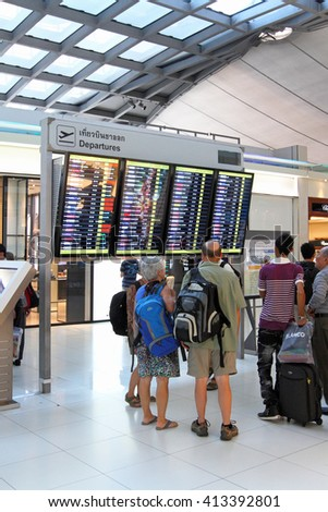 BANGKOK, THAILAND - MARCH 31, 2012: Tourists look at an information display of the airport - stock photo