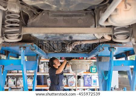 Bangkok, Thailand - March 28, 2016 : Unidentified serviceman checking a car for fix and repair at garage - stock photo