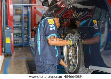 Bangkok, Thailand - March 20, 2016 : Unidentified serviceman checking suspension in a car at garage - stock photo