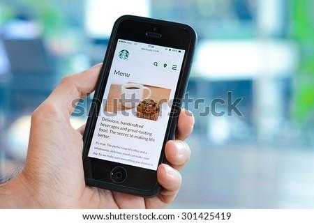 Bangkok, Thailand - May 20, 2015 : A man hand holding iphone with Starbucks menu web page on screen - stock photo