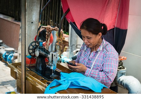 BANGKOK, THAILAND - 07 MAY 2014: Female street seamstress with old sewing machine on wooden bench using her phone. - stock photo