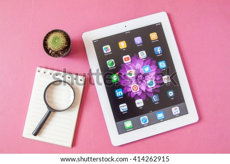 BANGKOK,THAILAND - May 2,2016: Social media icons on screen of iPad and iPhone. Social media are most popular tool for communication, sharing information and content between people in internet. - stock photo