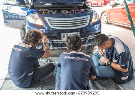 Bangkok, Thailand - May 6, 2017 : Unidentified car mechanic or serviceman checking a car headlight for fix and repair problem at car garage or repair shop