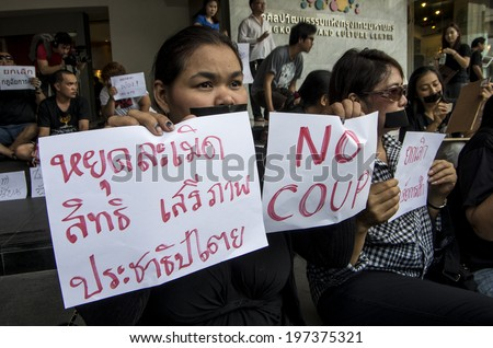 "BANGKOK, THAILAND - May 20, 2014: Unidentified demonstrators gagged themselves during a demonstrations on the first day of martial law. Left sign: ""Stop violating the right, freedom and democracy."""