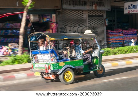 Bangkok, Thailand - May 23, 2014: Unidentified driver and tourists in tuk-tuk vehicle along the roads of Bangkok, Thailand. The tuk-tuk is a widely used form of urban transport in Bangkok. - stock photo