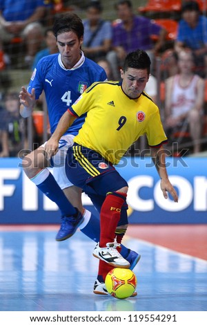 BANGKOK,THAILAND-NOV18: Andres Reyes  (yellow ) of Colombia control the ball during the FIFA Futsal World Cup  between Italy and Colombia at Indoor Stadium Huamark on Nov18,2012 in,Thailand. - stock photo