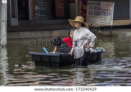 BANGKOK, THAILAND - NOV 5, 2011: People and dogs with their transportation during a big flooding in Thailand. At Phongphet junction, Ngamwongwan road. - stock photo