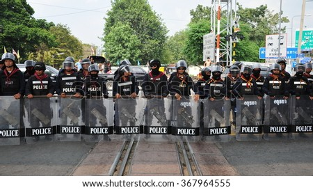 BANGKOK, THAILAND - NOV 11, 2013: Police officers in riot gear stand guard on a railway level crossing as thousands of anti government protesters rally through the Thai capital.