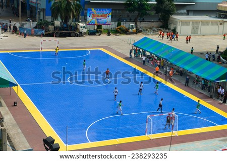 BANGKOK, THAILAND - 21 NOV 2013: Sportsmen train on blue outdoor stadium in front of sport science bureau of Sports Authority of Thailand (SAT) near National stadium - stock photo