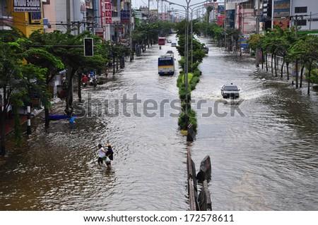 BANGKOK THAILAND- NOV 13: Unidentified people walk across flood street  on November 13, 2011 in Ekkachai Road, Bangbon, Bangkok, Thailand. - stock photo