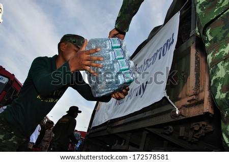 BANGKOK THAILAND- NOV 13: Unidentified soldier donate food and water for people on the bus on  flood street  on November 13, 2011 in Pra Pin Klao Brigde, Bangkoknoi, Bangkok, Thailand. - stock photo