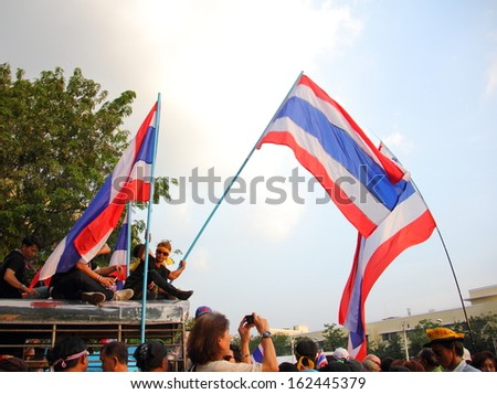 BANGKOK, THAILAND- NOVEMBER 11 : Against amnesty bill protesters weave Thai flag on car roof at Democracy monument, on November 11, 2013 in Bangkok THAILAND