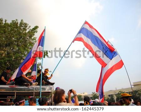 BANGKOK, THAILAND- NOVEMBER 11 : Against amnesty bill protesters weave Thai flag on car roof at Democracy monument, on November 11, 2013 in Bangkok THAILAND - stock photo