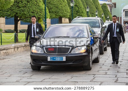 BANGKOK, THAILAND - NOVEMBER 17, 2013 : An unidentified body guards protect state automobile, which moves in the Grand Palace in Bangkok. - stock photo