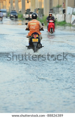 BANGKOK, THAILAND - NOVEMBER 04: An unidentified man riding motorcycle wade through flood in Bangkok on November 04, 2011 in Bangkok, Thailand.