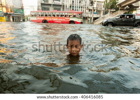 BANGKOK , THAILAND - NOVEMBER 2, 2011 :  Bangkok, Thailand 2011 during the big floods that affected several provinces of the country. Children enjoy flooded streets to bathe with big health risks.