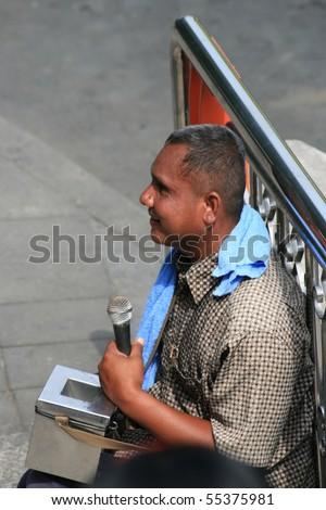 BANGKOK, THAILAND - NOVEMBER 29: Blind man sits and plays music for money by the road on November 29, 2008 in Bangkok. - stock photo