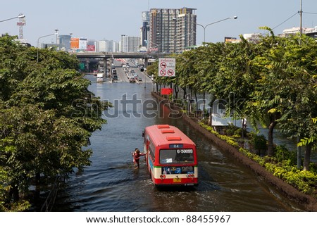 BANGKOK, THAILAND - NOVEMBER 04: Bus pick up people at a flooded street on November 04, 2009 in Bangkok, Thailand. During Thailand's worst monsoon flood in 20 years - stock photo