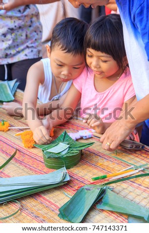 Bangkok , Thailand - 2 November, 2017: Child making the floating basket by banana leaf / banana leave vessel