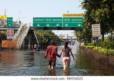 BANGKOK, THAILAND - NOVEMBER 04: Couple walking through a flooded street on November 04, 2009 in Bangkok, Thailand. During Thailand's worst monsoon flood in 20 years - stock photo