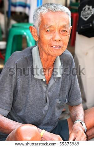 BANGKOK, THAILAND - NOVEMBER 29: Elderly Thai man sits begging for money in Chatuchak market on November 29, 2008 in Bangkok. - stock photo