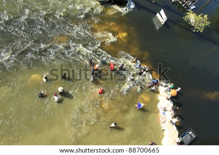 BANGKOK, THAILAND - NOVEMBER 13: Group of men destroying water barrier to open the water flow to opposite side during the worst monsoon flooding in decades in Bangkok, Thailand on November 13, 2011. - stock photo