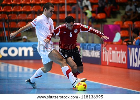 BANGKOK,THAILAND-NOVEMBER 03:Mostafa Nader (red) of Egypt for the ball during the FIFA Futsal World Cup between Egypt and Serbia at Indoor Stadium Huamark on Nov3,2012 in Bangkok,Thailand. - stock photo