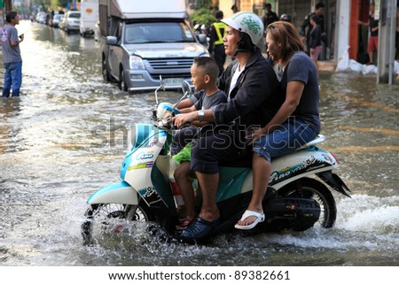 BANGKOK, THAILAND - NOVEMBER 17 : Motorbike navigates the floods after the heaviest rains in 20 years in Thailand on Nov 17, 2011 in Bangkok, Thailand