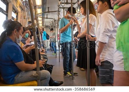 BANGKOK, THAILAND - NOVEMBER 17, 2015: Passengers inside the Bangkok Mass Transit System (BTS) public train in Thailand. - stock photo