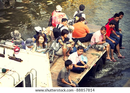 BANGKOK, THAILAND - NOVEMBER 12: People traveling together by truck on flooded streets on Nov 12, 2011 in Bangkok, Thailand