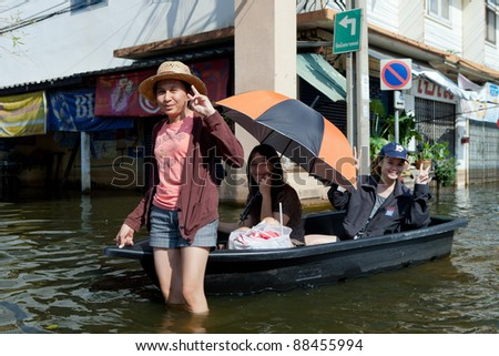 BANGKOK, THAILAND - NOVEMBER 04: People with a boat in a flooded street in Bangkok's suburb Bang Yi Khan on November 04, 2009 in Bangkok, Thailand. During Thailand's worst monsoon flood in 20 years - stock photo