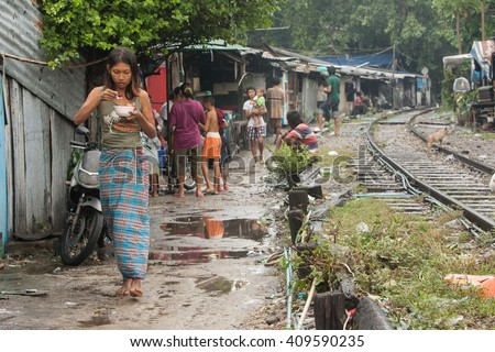 BANGKOK , THAILAND - NOVEMBER, 2005 :  There are an estimated 7.3 million people that are considered to be in poverty in Bangkok, Thailand. Many live along the railroad tracks or in slums  - stock photo