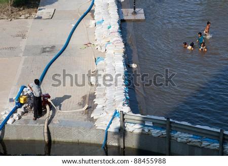 BANGKOK, THAILAND - NOVEMBER 04: unidentified Children swimming at a sandbag wall at the Chao Phraya river on November 04, 2009 in Bangkok, Thailand. During Thailand's worst monsoon flood in 20 years - stock photo