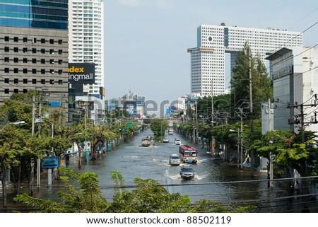BANGKOK, THAILAND - NOVEMBER 6: Various vehicles navigate through the flood on Phahonyothin Road during the worst flooding in Bangkok, Thailand on November 6, 2011. - stock photo