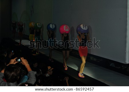 "BANGKOK, THAILAND - OCT 12 : A model is walking the runway at "" SFG  GHOES "" collection presentation during ELLE Fashion Week 2011 Autumn/Winter on October 12, 2011 in Bangkok Thailand."
