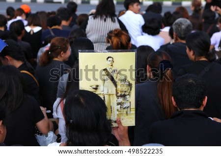 BANGKOK, THAILAND - OCT 14, 2016: A woman holds image mourners of Thailand's King Bhumibol Adulyadej the body is taken from Siriraj Hospital to Wat Phra Kaew on October 14, 2016 in Bangkok, Thailand.