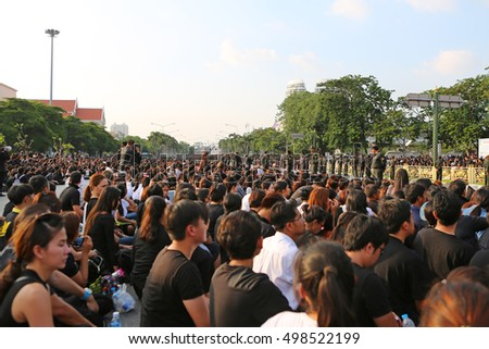 BANGKOK, THAILAND - OCT 14, 2016: Crowds of mourners at roadside while the body Thai King Bhumibol Adulyadej is taken from Siriraj Hospital to Wat Phra Kaew on October 14, 2016 in Bangkok, Thailand.