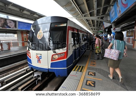 BANGKOK, THAILAND - OCT 8, 2013: Rail travellers wait for an approaching BTS Skytrain at a city centre station. The Thai capital's BTS rail public transport system serves 600,000 passengers daily. - stock photo