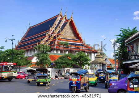 BANGKOK, THAILAND - OCT 30: Traffic of colorful taxi and tuk-tuk in front of Wat Pho, October 30th 2009, Bangkok, Thailand - stock photo