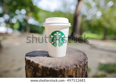 Bangkok ,Thailand - OCTOBER 11, 2016 : A cup of Starbucks hot beverage coffee on the wood log in the park. Starbucks is the world's largest coffeehouse company