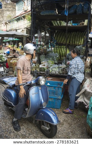 BANGKOK, THAILAND - OCTOBER 27, 2014: A customer pulls up on his scooter to make a purchase from a vendor at the outdoor fruit and vegetable market.