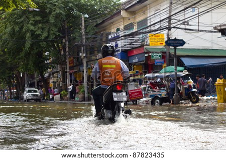 BANGKOK THAILAND - OCTOBER 29 : An unidentified man riding a scooter through the water during  flood at Tha Chang road on October 29, 2011 Bangkok, Thailand.